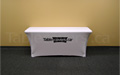 White 6 foot economy spandex table cover with black logo